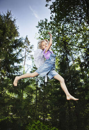 dressups: Girl wearing wings and jumping in forest