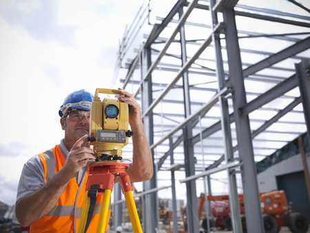 Construction worker surveying site