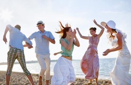 personas reunidas: Gente bailando juntos en la playa