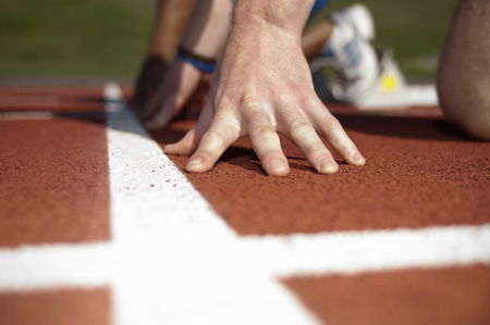 Close up of athletes hand on track