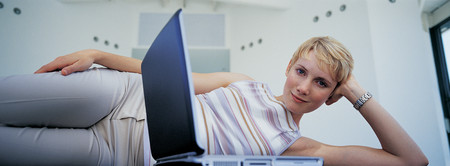 telecommuter: Woman laying on floor with laptop