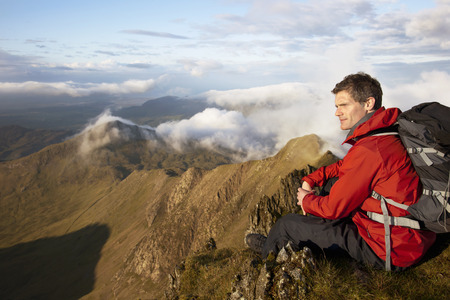 remoteness: Hiker overlooking view from mountaintop