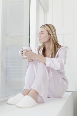 Woman having cup of coffee in pajamas