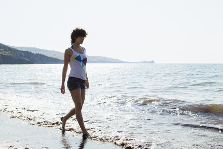 Woman walking in waves on beach LANG_EVOIMAGES