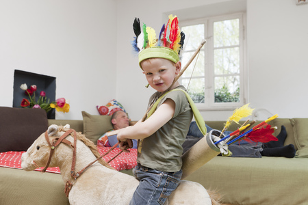 dressups: Boy in war bonnet playing with toys LANG_EVOIMAGES