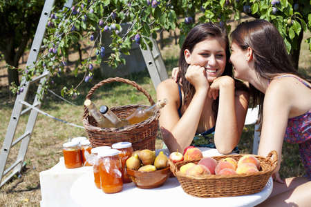 ceasing: Smiling women picnicking in orchard LANG_EVOIMAGES