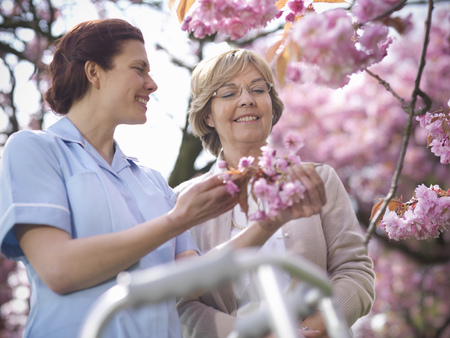 faiths: Older woman with caretaker and blossoms