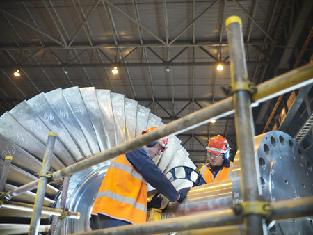 Workers inspect turbine in power station LANG_EVOIMAGES