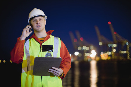 acknowledging: Worker talking on cell phone in shipyard