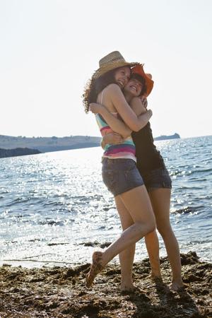 Women in sunhats hugging on beach LANG_EVOIMAGES