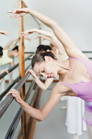 rehearse: Ballet dancers posing at barre