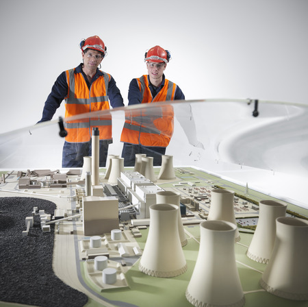 Workers examining model of power station LANG_EVOIMAGES
