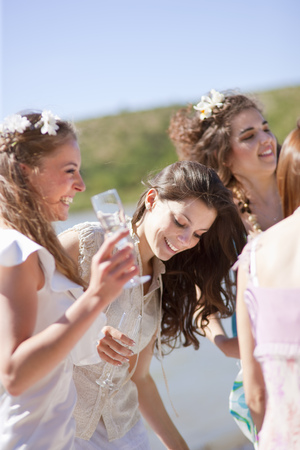 Bride drinking champagne with friends