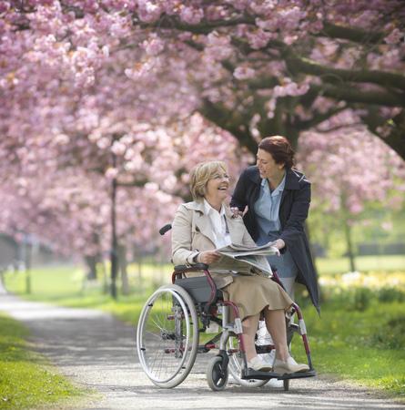 transportation: Older woman with caretaker in park