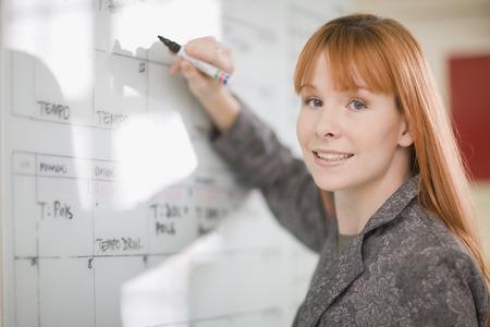 Businesswoman writing on calendar LANG_EVOIMAGES