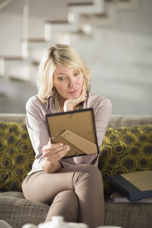 mournful: Woman admiring framed photo on couch