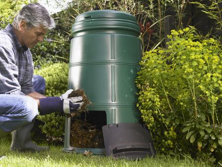 Man composting in backyard
