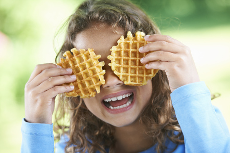 enclose: Smiling girl playing with waffles
