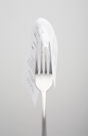 expenditure: Close up of receipt on fork