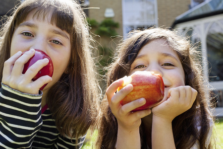 morsels: Girls eating apples outdoors