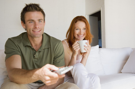 remote controls: Couple watching television together