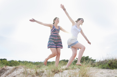 pursuing: Women playing airplane on beach LANG_EVOIMAGES
