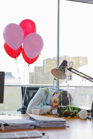 Businessman asleep at desk after party LANG_EVOIMAGES