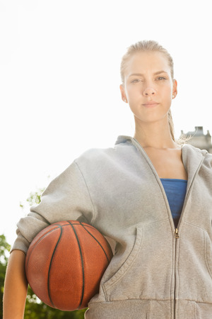 Woman carrying basketball outdoors LANG_EVOIMAGES