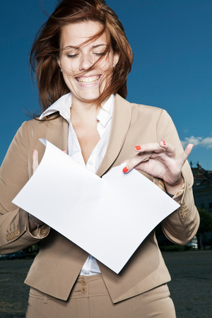 tearing down: Businesswoman ripping paper outdoors