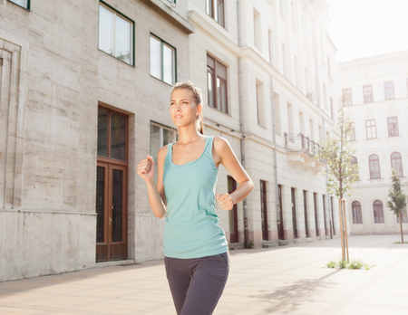 physically fit: Runner jogging on city street