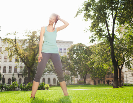 physically fit: Woman stretching in urban park