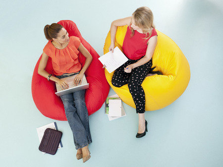 Businesswomen working in bean bag chairs LANG_EVOIMAGES