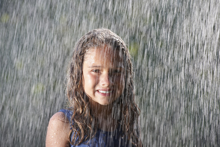 saturating: Smiling girl playing in rain