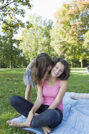 confide: Mother and daughter whispering outdoors