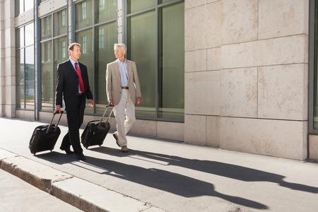 shadowed: Businessmen rolling luggage outdoors LANG_EVOIMAGES