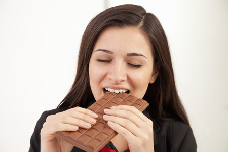 avarice: Businesswoman eating bar of chocolate LANG_EVOIMAGES