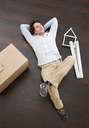 lays down: Man laying on floor with boxes