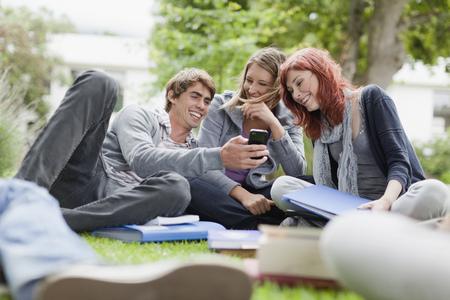 reconocimientos: Estudiantes usando el teléfono celular en el césped LANG_EVOIMAGES