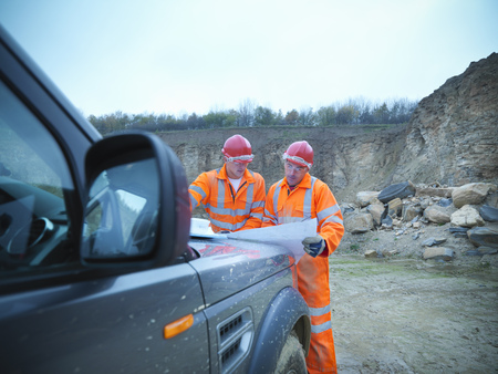 review: Workers reading blueprints in quarry