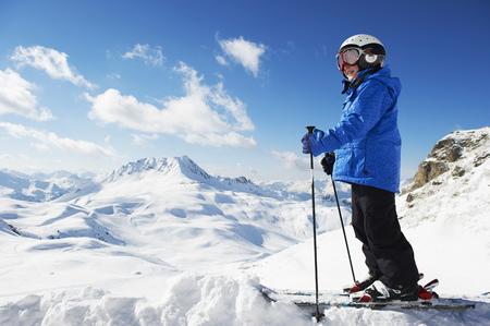 mountainous: Boy in skis on snowy mountaintop
