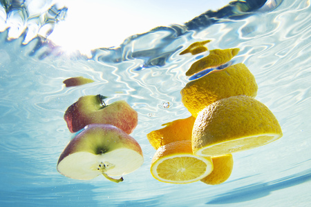 uncomplicated: Fruit floating in swimming pool LANG_EVOIMAGES