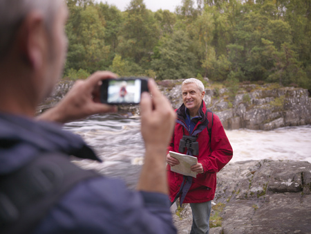 rushed: Hiker taking picture of friend by river LANG_EVOIMAGES