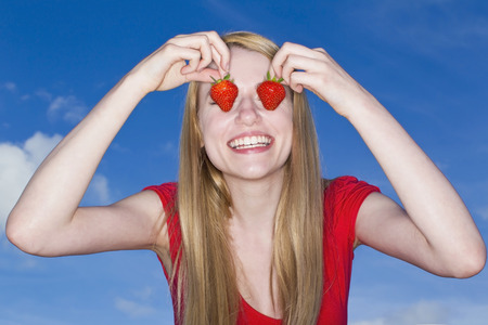 Woman holding strawberries over eyes LANG_EVOIMAGES