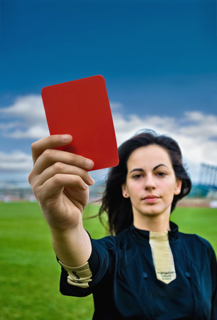 warned: Woman holding red card on soccer pitch