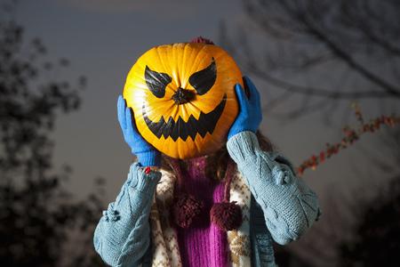 Woman holding jack oí lantern over face