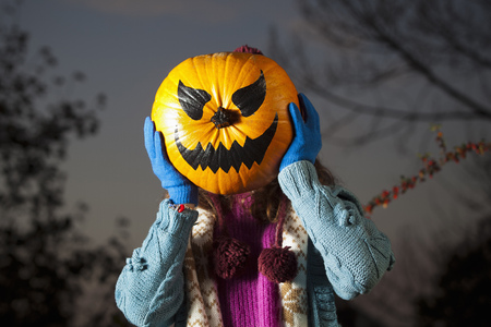 whimsy: Woman holding jack oí lantern over face