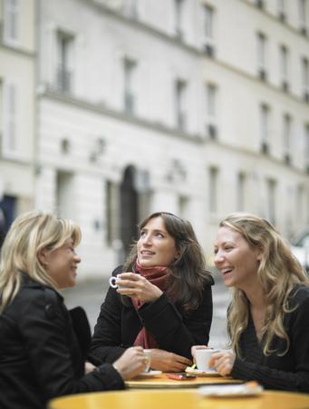 talker: Women having coffee at sidewalk cafe LANG_EVOIMAGES