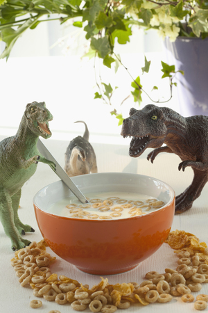 Toy dinosaurs with bowl of cereal
