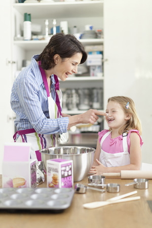 mischeif: Mother and daughter baking in kitchen