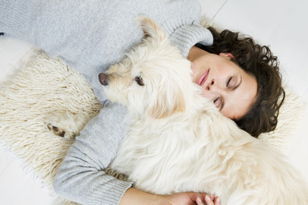 Woman relaxing with dog on rug